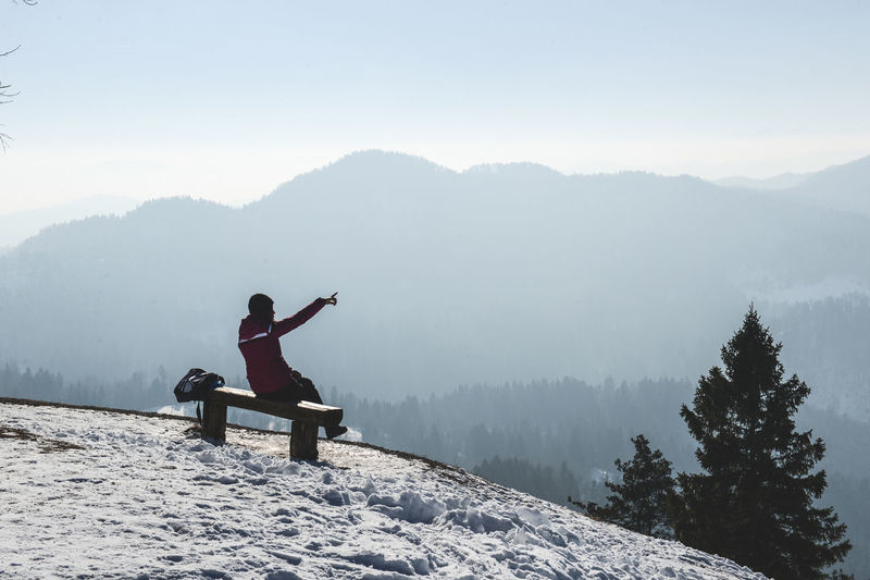 Woman pointing while sitting on bench at snowcapped mountain