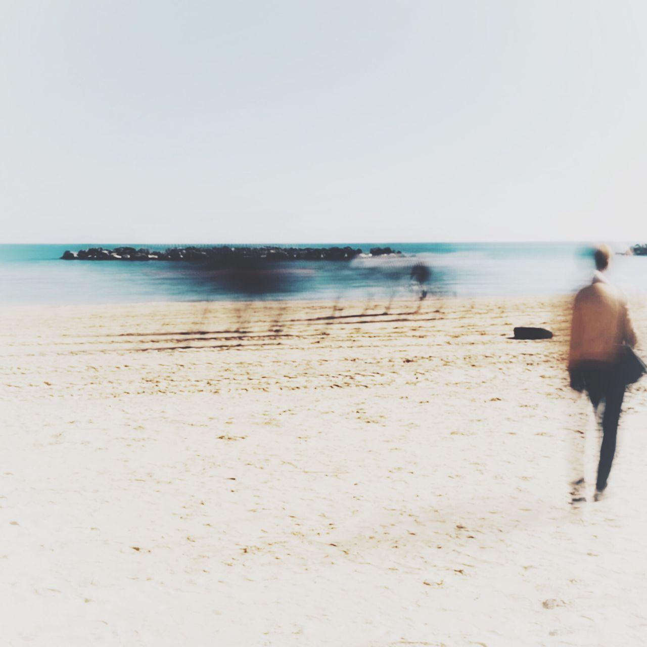 PEOPLE WALKING ON BEACH AGAINST CLEAR SKY