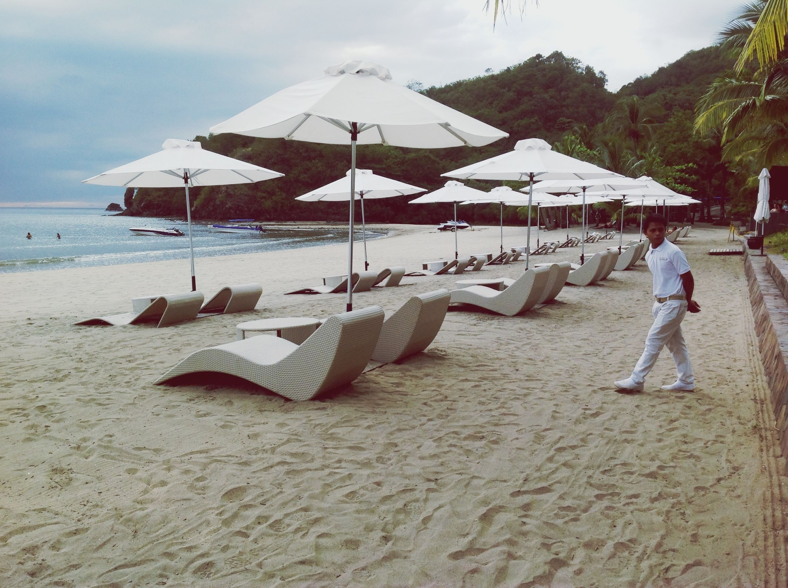 beach, sand, shore, sky, water, sea, mountain, tranquility, vacations, tranquil scene, nature, incidental people, day, scenics, outdoors, beach umbrella, leisure activity, beauty in nature, travel destinations