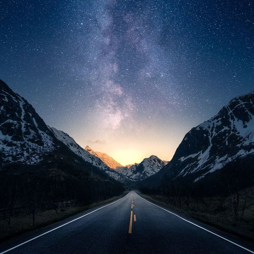 Empty road amidst mountains against sky at night