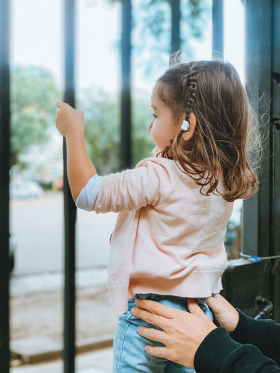 Girl looking away while standing against window