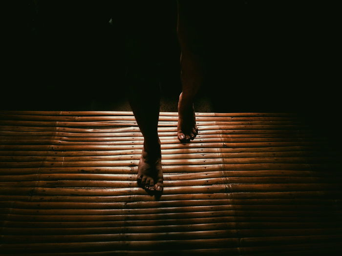 Low section of woman standing on bamboo mat in dark