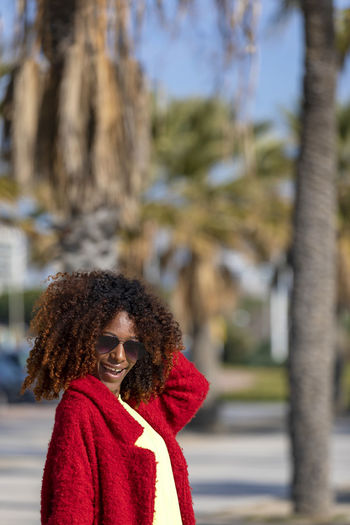 Front view of young beautiful curly woman standing on path smiling while looking camera in sunny day One Person Curly Hair Portrait Focus On Foreground Real People Lifestyles Red Clothing Standing Women City Hairstyle Leisure Activity Day Tree Young Adult Young Women Waist Up Hair Outdoors Warm Clothing Woman African American Afro Denim Happiness Happy Fun Daylight Sunlight