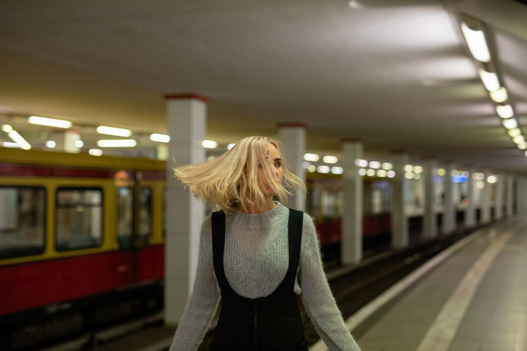 Woman with blond hair standing at railroad station platform