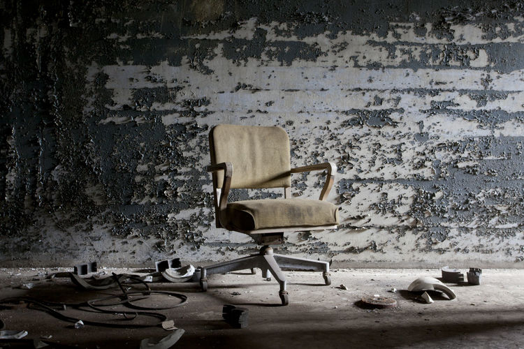 Abandoned chairs in front of wall