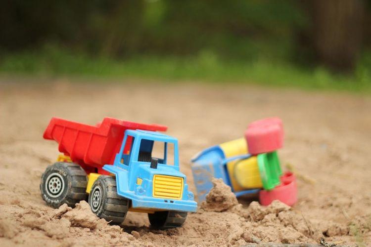 Toy trucks on muddy field