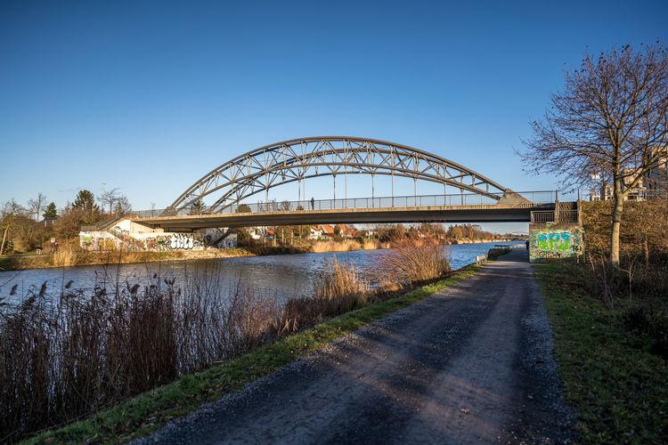Bridge over river against clear blue sky