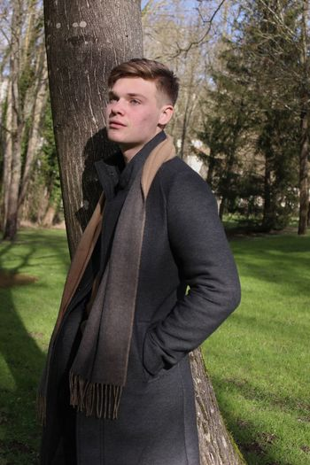 Handsome young man standing by tree in park