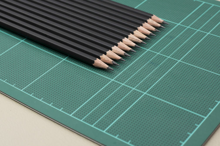 Close-Up Of Pencils On Paper Cutting Mat