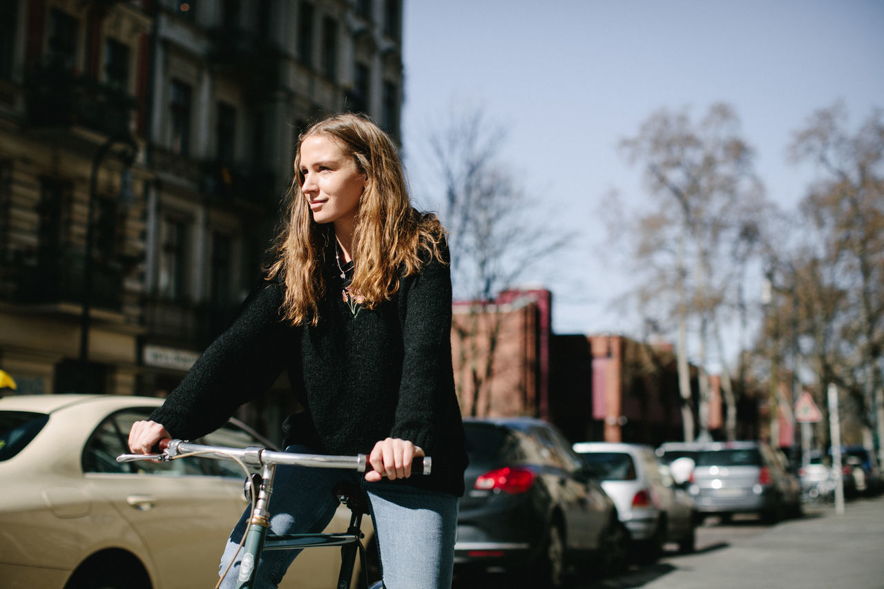 Smiling young woman with bicycle on street in city