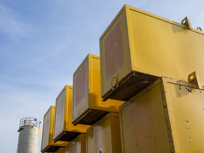 Low angle view of yellow construction containers against sky