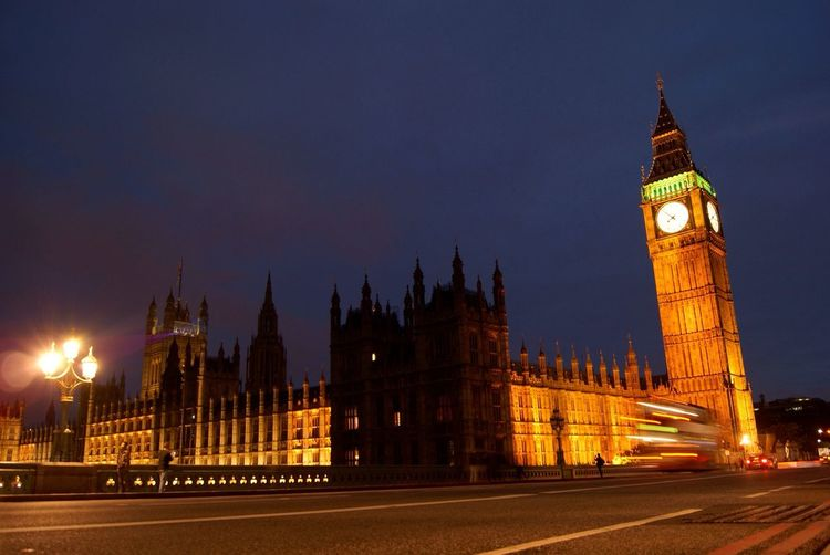 City street by illuminated big ben and houses of parliament against sky at night