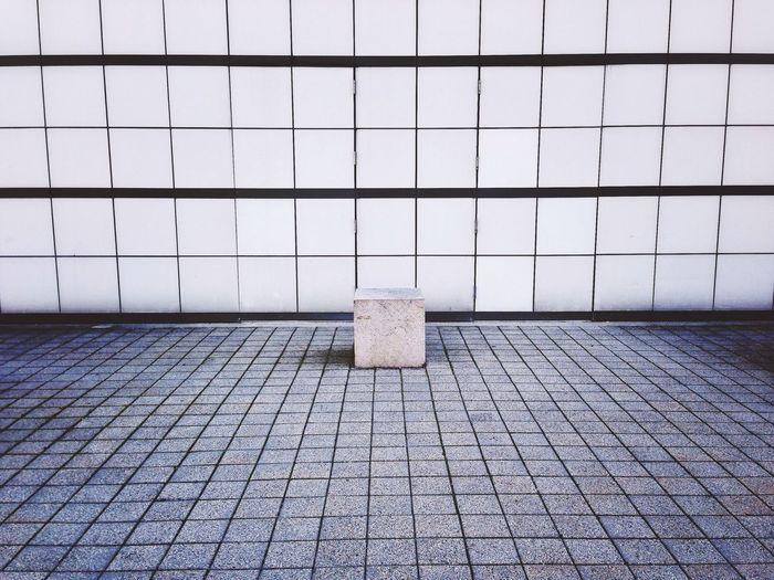 Sidewalk against tiled wall