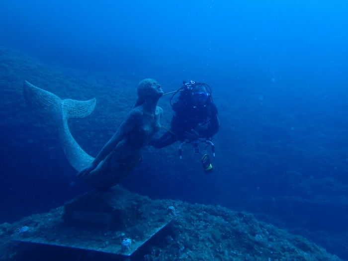 Man scuba diving by sculpture in sea