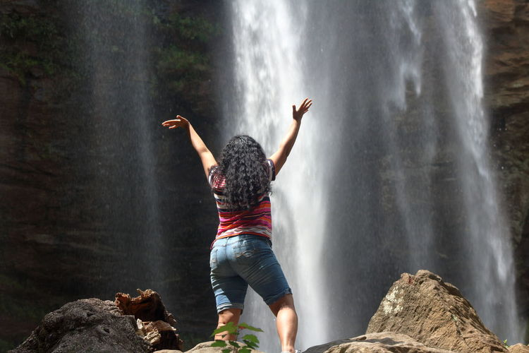 Arms Raised Beauty In Nature Casual Clothing Day Flowing Water Freedom Human Arm Human Limb Leisure Activity Lifestyles Limb Long Exposure Motion Nature One Person Outdoors Real People Rear View Rock Rock - Object Scenics - Nature Solid Waterfall