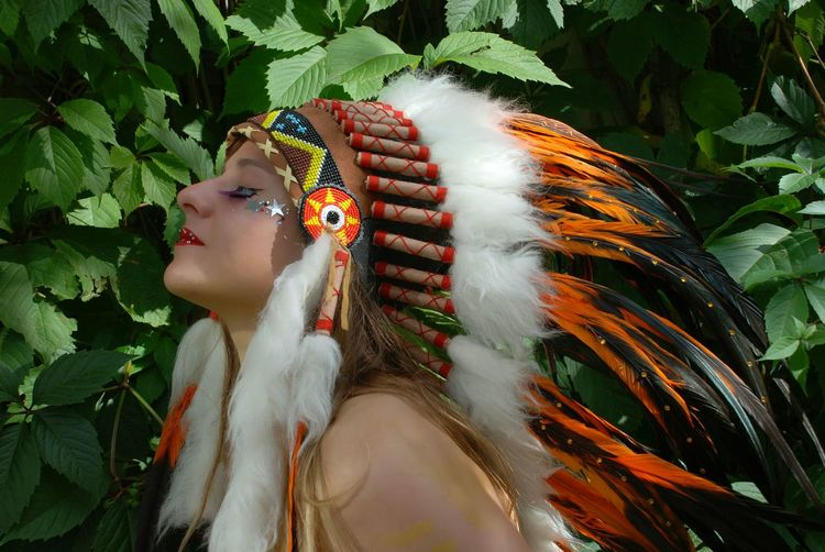 Close-up of young woman wearing headdress against plants