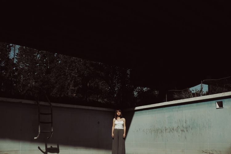 Woman standing by swimming pool at night