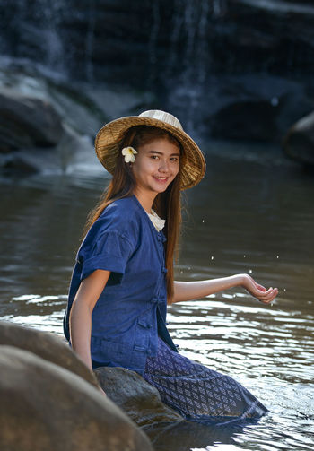 Portrait Of Young Woman Wearing Straw Hat In Forest