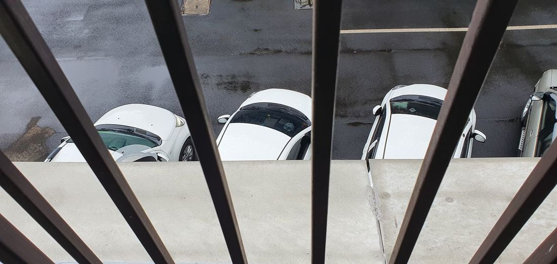 High angle view of cars parked on street seen through window
