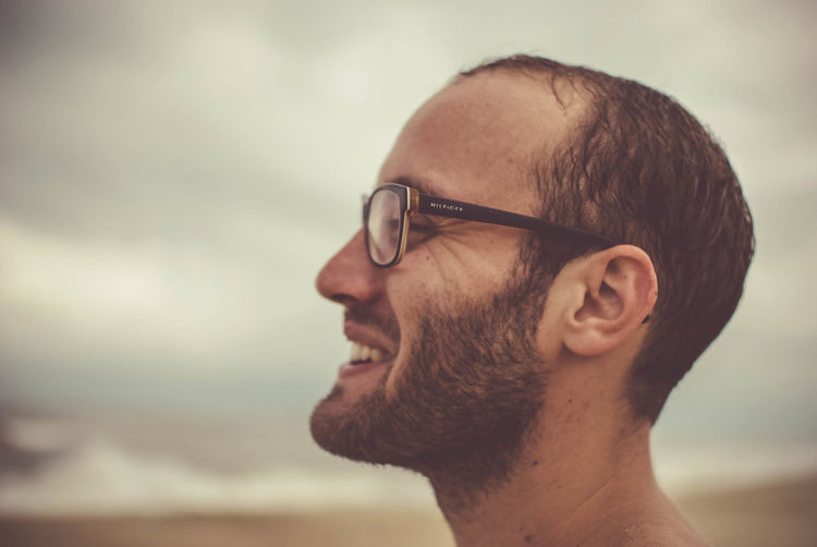 Side view of young man wearing sunglasses against sky