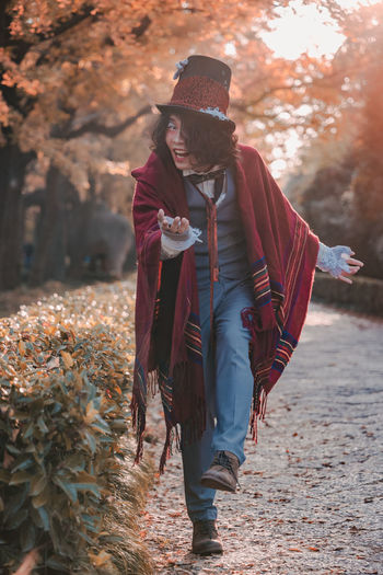 Man cosplaying mad hatter bowing on path next to hedges in autumn