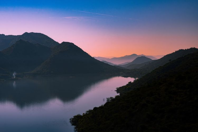 Scenic view of lake and mountains against sky during sunrise