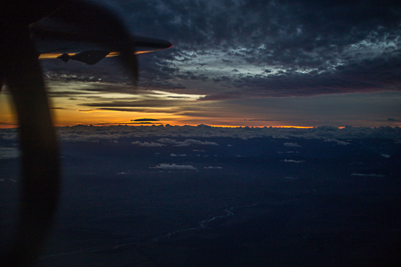 Cropped Image Of Airplane Flying Against Cloudy Sky During Sunset