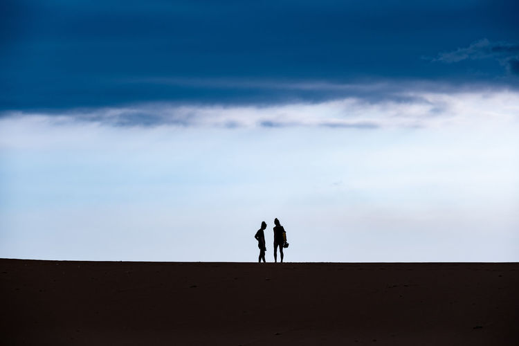 The sky, people and ground. Sky Cloud - Sky Land Two People Real People Leisure Activity Nature Silhouette Men Togetherness Beauty In Nature Sand Lifestyles Tranquil Scene Tranquility Scenics - Nature People Standing Women Adult Outdoors Arid Climate Couple - Relationship Climate