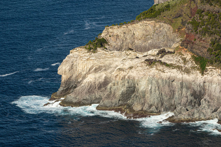 Splashing waves on rocky cliffs. atlantic ocean at sao miguel island, azores, portugal
