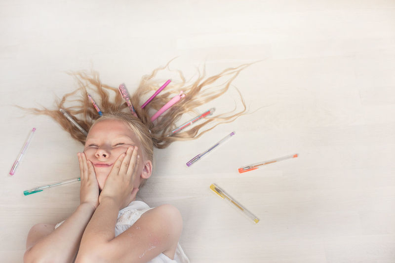 High angle view of girl lying on floor with pens