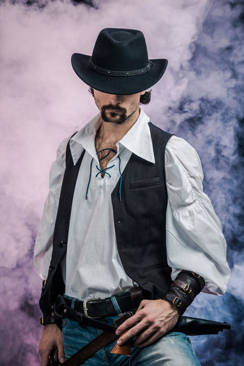 Handsome young man. This is an American cowboy. A vow to a white shirt, brown waistcoat and blue jeans. Black shoes on the feet. Carries a shtyapa, on a belt two pistols. The hair is of medium length; on the face is a beard and mustache. Authentic photo. Culture of America. Cowboy Wild West America American Gun National Authentic Moments Lifestyles Lifestyle One Person Candid Authentic Hat Clothing Front View Three Quarter Length Men Real People Standing Beard Young Men Young Adult Waist Up Males  Facial Hair