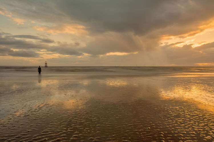 """Rain clouds in the distance at low tide at Crosby Beach in front of Antony Gormley's """"Another Place"""", Liverpool, England, UK. Another Place Another Place On Crosby Beach Crosby Beach England, UK Liverpool, England Sunset Silhouettes Wet Sand Reflection Another Place By Anthony Gormley Beach Low Tide Rain Clouds Reflections In The Water Shower Clouds"""