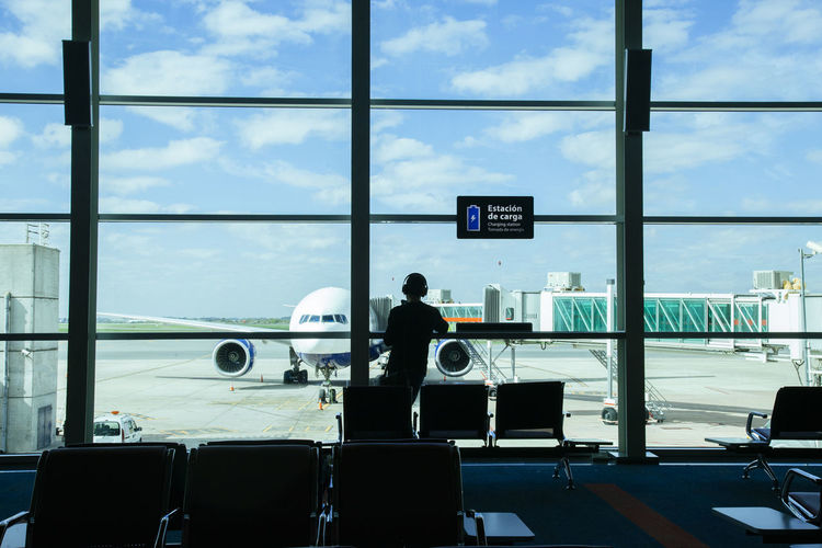 Rear view of man standing in waiting room at airport