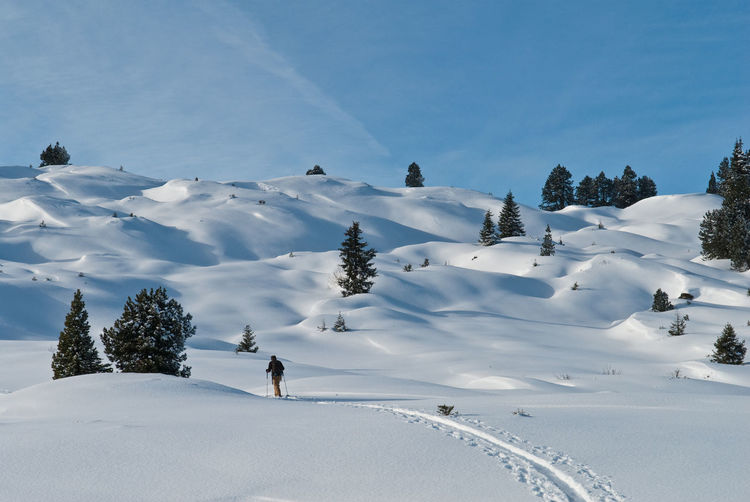 Man walking on snow covered land against sky