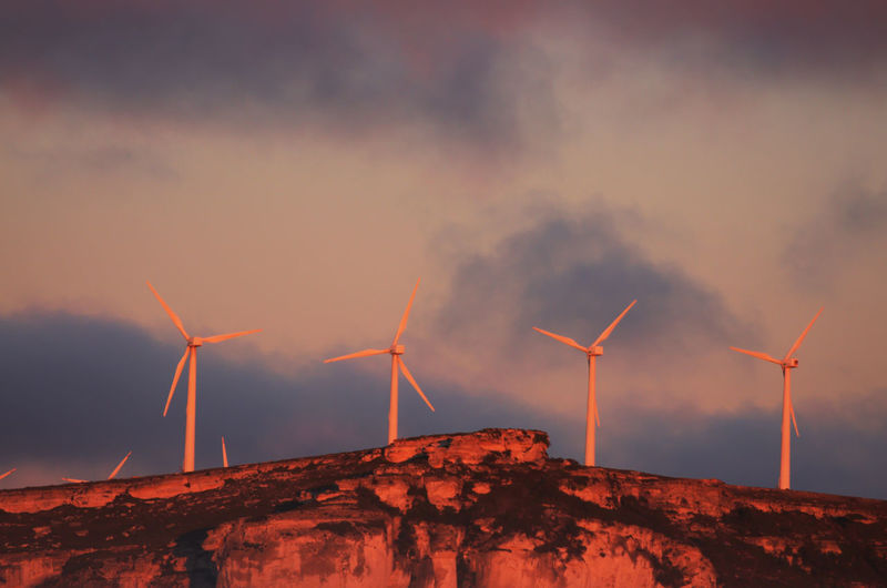 Low angle view of windmills on mountain against cloudy sky during sunrise