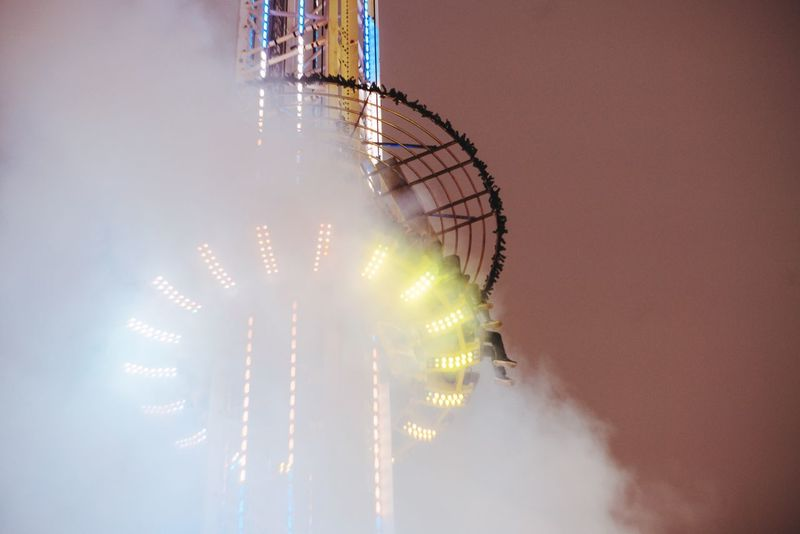 Mysterious appearance Arts Culture And Entertainment Amusement Park Low Angle View Amusement Park Ride Outdoors No People Big Wheel Freefall Free Falling Gyro Drop Christmastime Night Lights UFO Unrecognizable Person Foggy Smoke Minimalism Colorful Capture Berlin My Year My View Thrill Rides Theme Park Christmas Market Structure Vertical