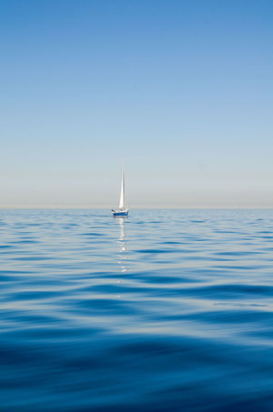 Beauty In Nature Blue Boat Calm Clear Sky Copy Space Horizon Over Water Nature Nautical Vessel Non-urban Scene Ocean Outdoors Rippled Sailboat Scenics Sea Seascape Surface Level Tourism Tranquil Scene Tranquility Transportation Vacations Water Waterfront