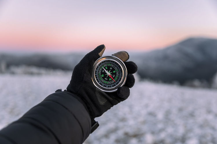 Close-up of explorer survival man holding a magnetic compass against sky during sunset.winter season