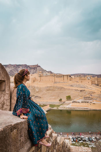 Woman Looking At Lake And Fort In City