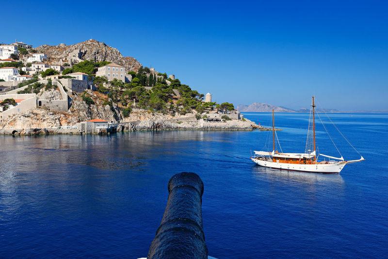 Sailboat sailing on sea against clear blue sky