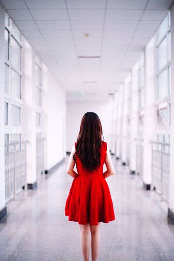 Rear View Of Young Woman Standing In Corridor