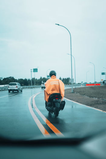 Rear view of man cycling on street