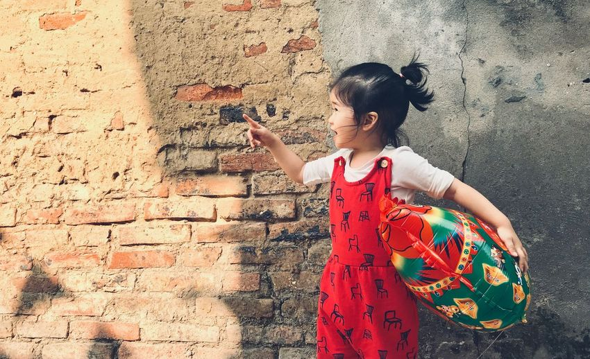 Baby girl holding balloon while standing against brick wall