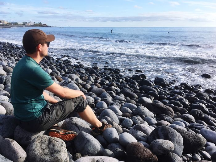 Man sits at rocky beach Canary Islands SPAIN La Gomera Vacation Travel Looking Sea Man Beach Beauty In Nature One Person Real People Lifestyles Horizon Sky Horizon Over Water Leisure Activity Scenics - Nature Sitting Nature Casual Clothing Pebble