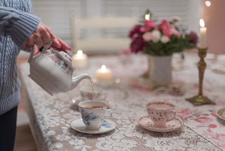 Midsection Of Woman Pouring Tea On Table At Home