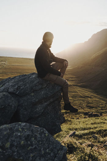 Man sitting on rock against sky