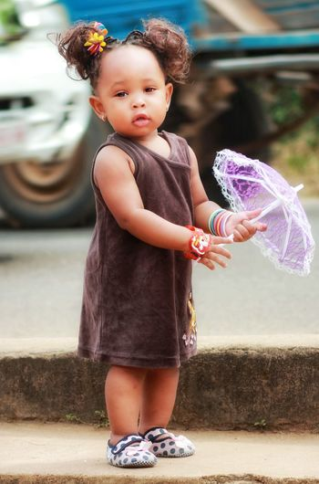 Portrait of cute girl holding toy umbrella while standing on sidewalk