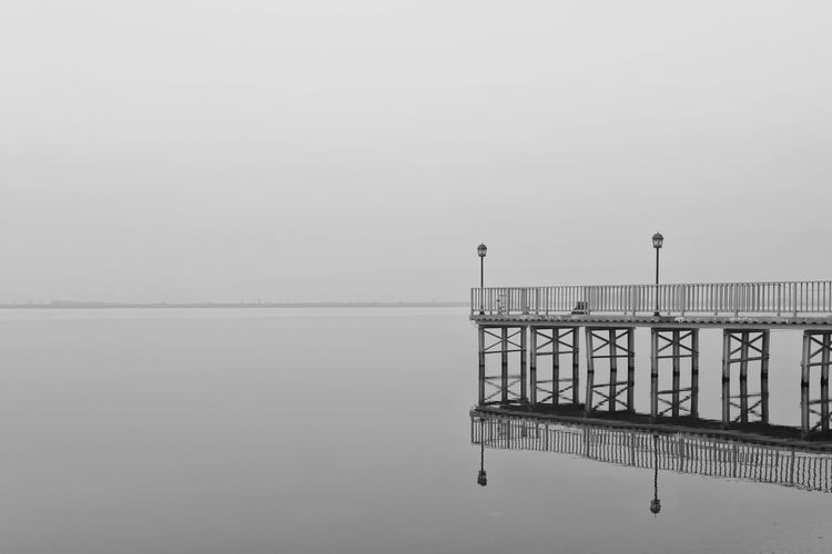 Pier by calm lake against sky