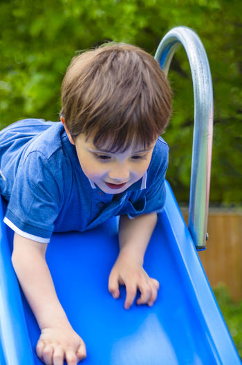 A young boy at the top of a garden slide. Blue T-shirt Boy Brown Hair Brown Haired Child Childhood Day Elementary Age Enjoyment Fun Garden Innocence Leisure Activity Outdoors Playful Playing Slide Sliding Young