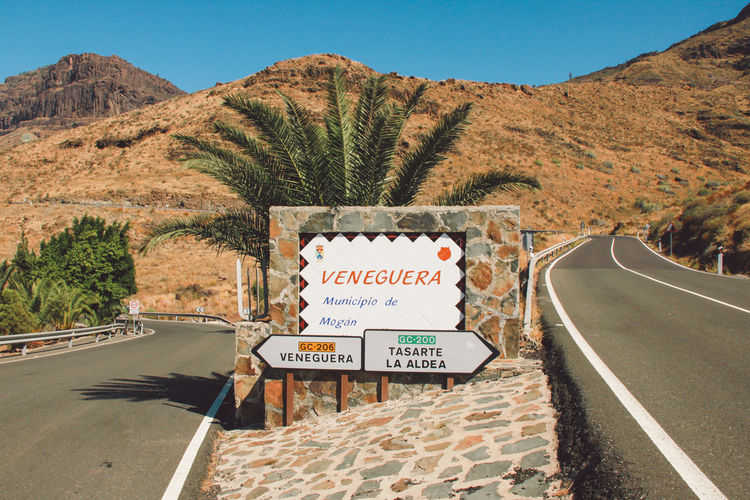 Canary Islands Gran Canaria Gran Canary Island SPAIN Travel Beauty In Nature Clear Sky Communication Day Landscape Mountain Mountain Range Nature No People Outdoors Road Road Sign Scenics Signboard Sky Text The Way Forward Transportation Tree Welcome Sign Western Script